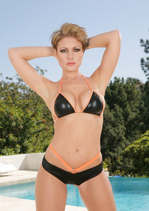Busty blond MILF pornstar Velicity Von poses beside swimming pool in bikini