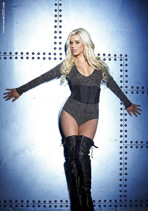 Blonde bombshell Spencer Scott posing fully clothed in stripper boots