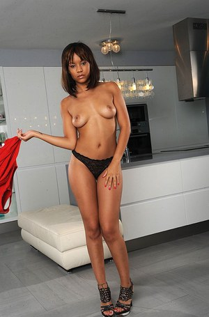 Ebony pornstar Sasha T posing fully clothed in red dress before undressing