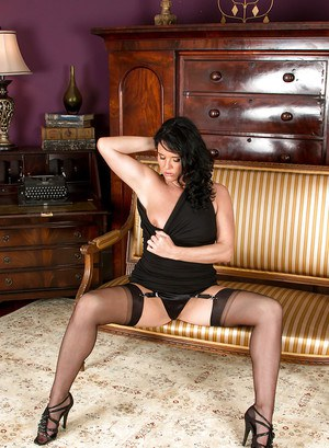 Older brunette babe Leah strikes sexy poses in garters and stockings
