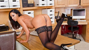 Leggy brunette pornstar Tiffany Brookes posing on desk in black nylons