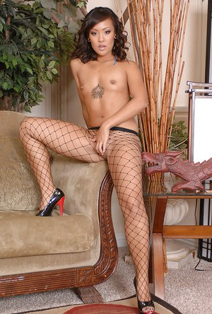 Exotic Oriental solo model Jandi showing off puffy pussy under fishnet