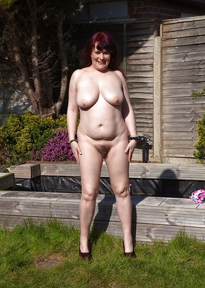 Older chubby Christina X baring big saggy boobs and beaver outdoors