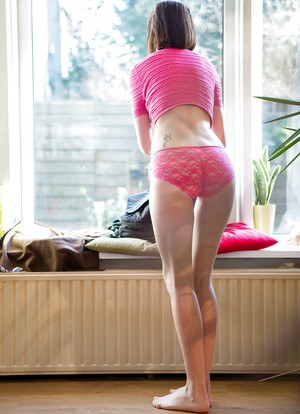 Petite older woman Bonnie C pulling on lace underwear and skirt