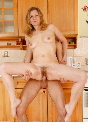 Skinny blonde cougar Kelli getting undressed for sex by younger man