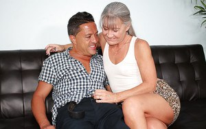 Grey haired cougar jerks off a younger man's penis until jizz flows
