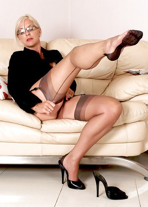 Fully clothed older businesswoman slips off pumps to reveal stocking feet