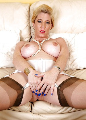 Mature Euro woman in nylons and garters exposes large breasts