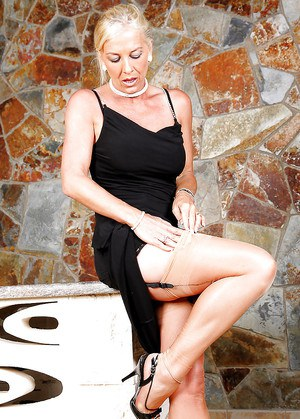 Leggy blonde woman Amazing Astrid strips down to lingerie to have a cig