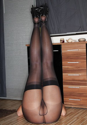 Sexy brunette mother Desyra Noir poses fully clothed in stockings and heels