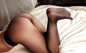 European lady Desyra Noir modeling topless on bed in black nylons