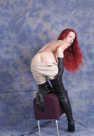Redhead chick in riding pants and poses in leather boots and gloves