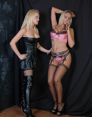 Blonde domme in thigh boots uses crop on blonde slave woman in garters