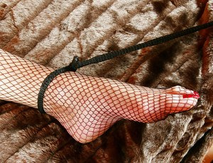Lady Sarah and fishnet clad submissive engage in lezdom sex games