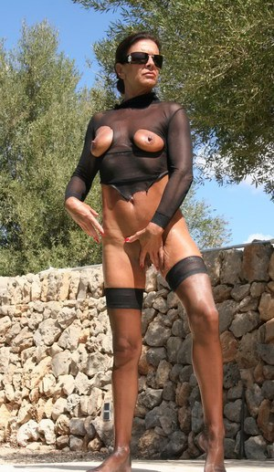 Mature UK chick Lady Sarak modeling exposed pussy outdoors in nylons