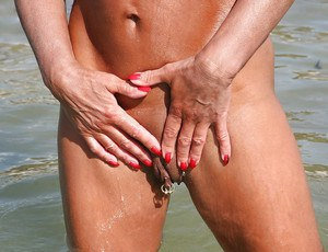 Nude UK woman Lady Sarah showing off pierced mature pussy outdoors on beach