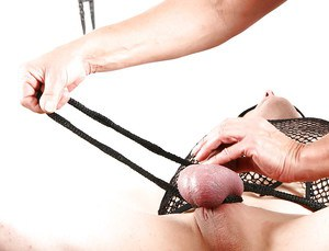 European domme Lady Sarah delivering CBT to bound submissive man