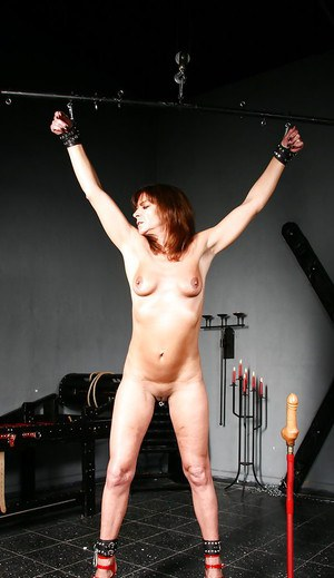 Mature slut Lady Sarah being used and abused in dungeon for sex slaves
