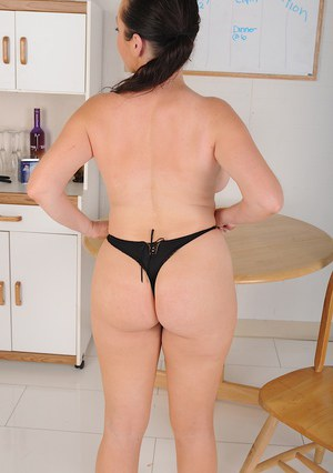 Naughty brunette MILF Tamara Fox posing topless in kitchen