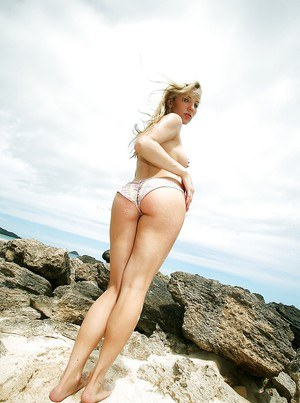 Blonde beach babe Ashley Fires modeling topless in bikini bottoms
