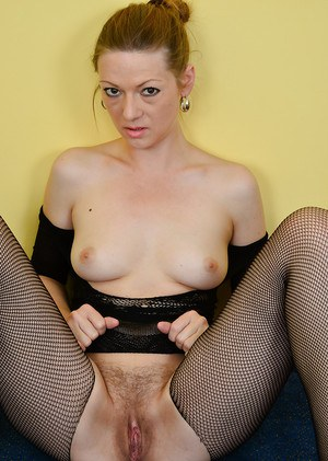 Older solo model Mischelle posing seductively in crotchless pantyhose