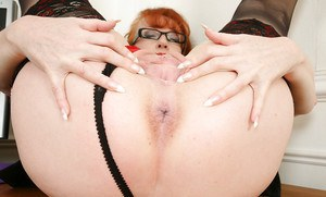 Mature redheaded woman Red posing for naughty pictures on desk