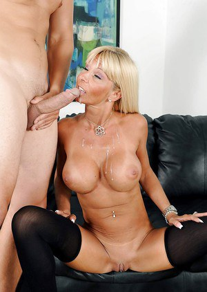Buxom blonde cougar Kasey Storm receiving oral sex on leather couch
