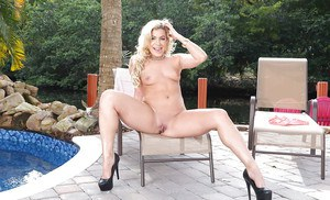 Curvy blond mom Nikki Capone strutting beside swimming pool in bathing suit