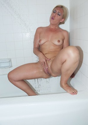 Mature blonde woman Stevie Lix taking a shower and spreading bald cooter
