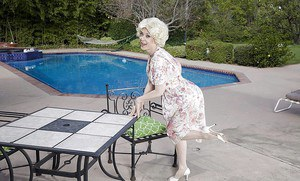 Mature pornstar Nina Hartley modelling outdoors in garters and nylons