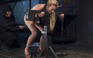 Petite blonde Emma Haize getting caned in stocks with panties around ankles