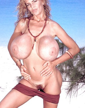 Chesty mature beach model Busty Dusty stripping off bikini outdoors