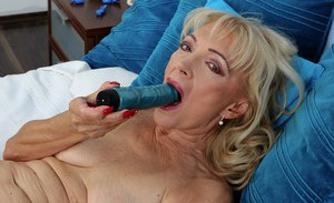 Mature woman Janet Lesley removing lingerie before toying shaved pussy