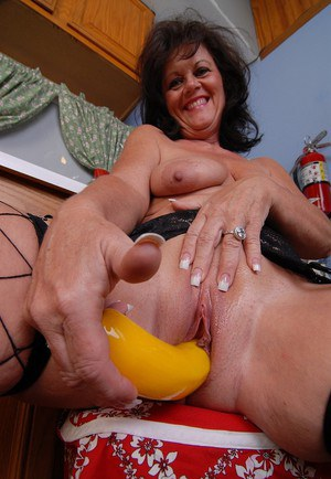 Mature brunette solo girl Debella toying shaved cunt in kitchen