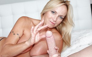 Busty mature blonde undresses to give big cock a Gonzo styled handjob