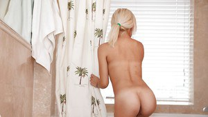 Voyeur catches blonde babe Ivy Stone exposing tiny tits and ass in bath