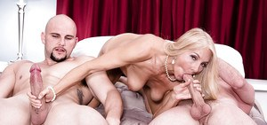 Over 50 blonde cougar Chery Leigh blowing two cocks in MMF threesome