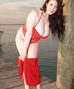 Chubby brunette Angela White unleashing large all natural tits on dock