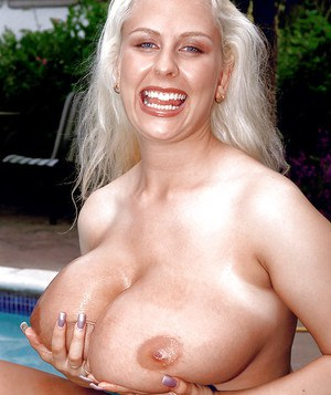 Blonde MILF solo girl Julia Miles oiling up huge knockers outdoors by pool