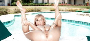 Flexible mature babe Venera oiling up huge juggs outdoors by swimming pool