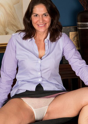 Mature model Kaysy exposing underwear and lingerie while undressing