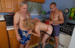 Mature threesome in kitchen with stocking clad Dana taking cum on tits
