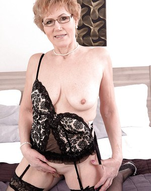 Glasses and stockings attired mature lady spreading pussy in high heels