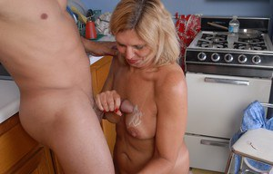Mature blonde in high heels gets on knees for cumshot on breasts in kitchen