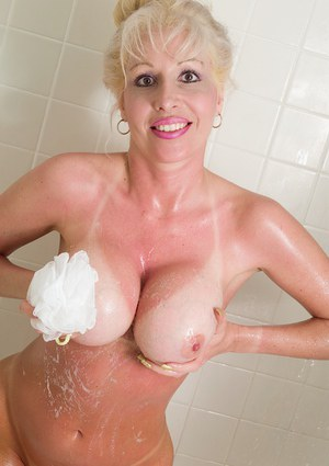 Wet older blonde plays with big mature breasts and nipples in shower
