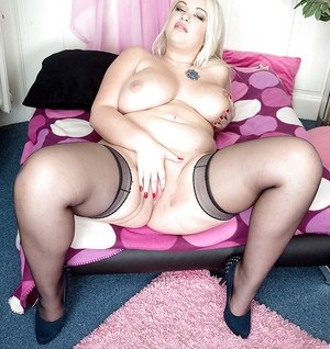 Blonde BBW in stockings and lingerie frees big tits before toying bald twat