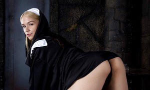 Blonde babe Sara Sloane strips off nun's uniform to expose big tits