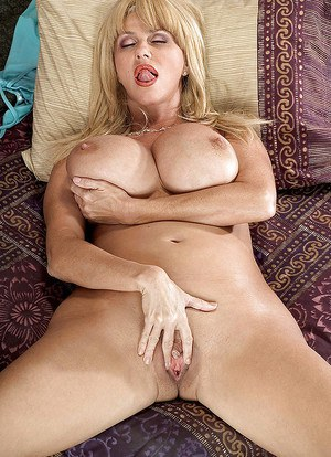 Mature babe Penny Porsche exposes huge hooters before spreading bald pussy