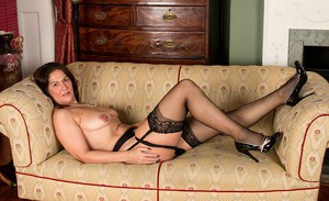 Aged brunette woman in stockings and garters unleashes big natural tits