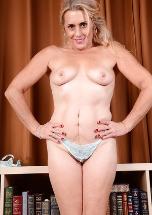 Older lady Cristine Ruby bares small tits before stretching hairy pussy